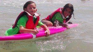 Una xiqueta saharaui amb una valenciana aprenent surf